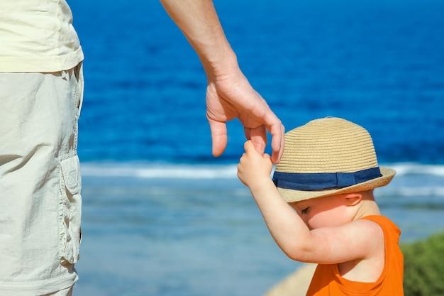 Ręce dziecka i rodzica na wakacjach nad morzem.