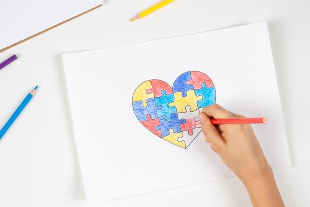 Ręce dziecka kolorowanki puzzle serce z kolorowymi kredkami światowy dzień świadomości autyzmu koncepcja