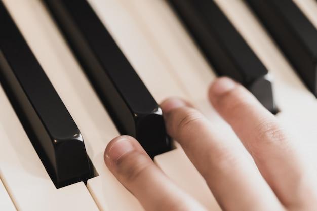 Ręce dziecka na klawiszach fortepianu grających na klawiszach fortepianu