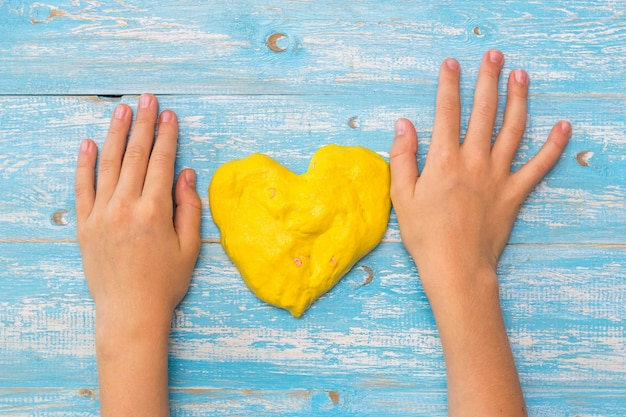 Ręce dziecka na stole z żółtym śluzem w formie serca. zabawka antystresowa. zabawka rozwijająca motorykę dłoni.