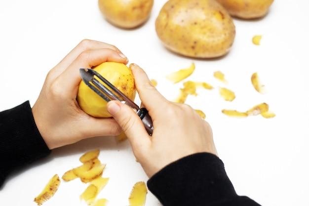 Ręce dziecka obierania ziemniaków obieraczką w kuchni, pomocna dłoń. zamknij zdjęcie