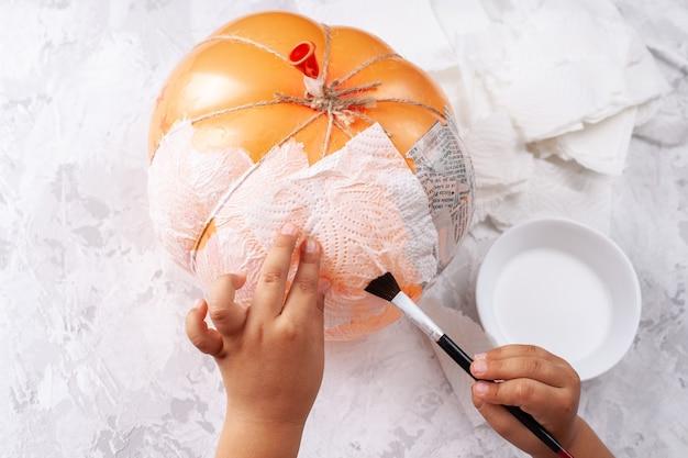 Ręce dziecka przyklejają kawałki papieru do balonu, hobby na izolacji, dynia z papier mache.