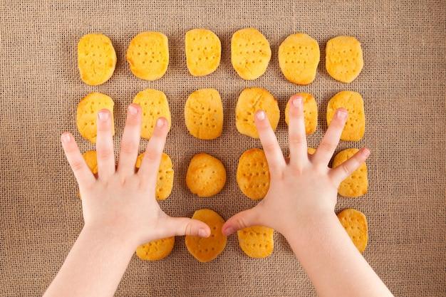 Ręce dziecka sięgają po ciasteczka bezglutenowe. domowe biszkopty leżą na płótnie. styl rustykalny.