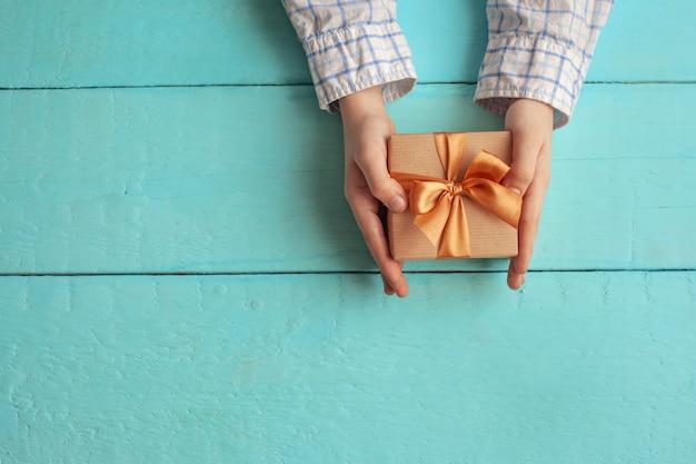 Ręce dziecka trzymają pudełko na prezenty zawinięte w papier rzemieślniczy i przewiązane kokardą.