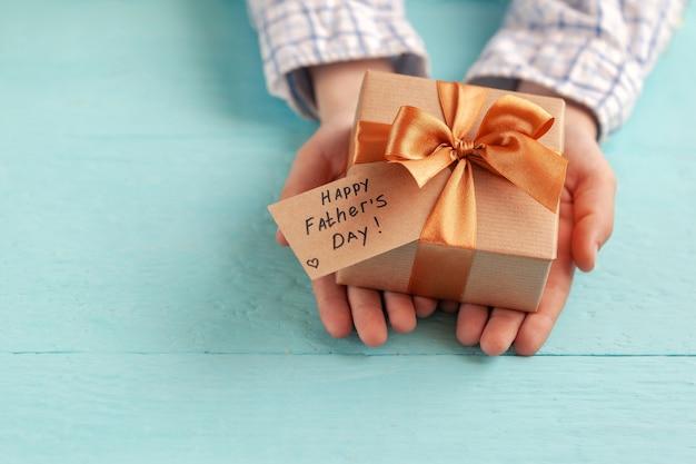 Ręce dziecka trzymają pudełko upominkowe owinięte papierem rzemieślniczym i przewiązane kokardą.