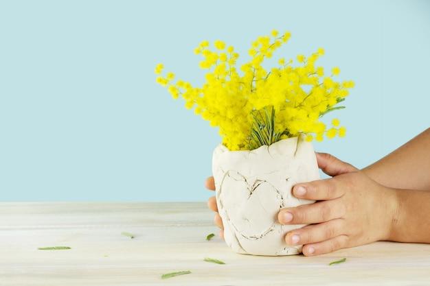 Ręce dziecka trzymające ceramiczny wazon z żółtymi kwiatami. na białym tle na niebieskiej powierzchni.