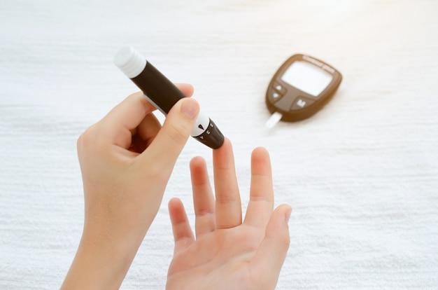 Ręce dziecka używające lancetu na palcu, aby sprawdzić poziom cukru we krwi za pomocą glukometru