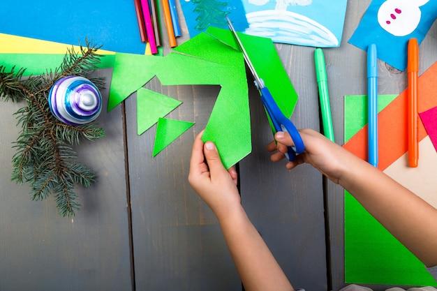 Ręce dziecka wykonują ręcznie robione świąteczne zabawki z tektury