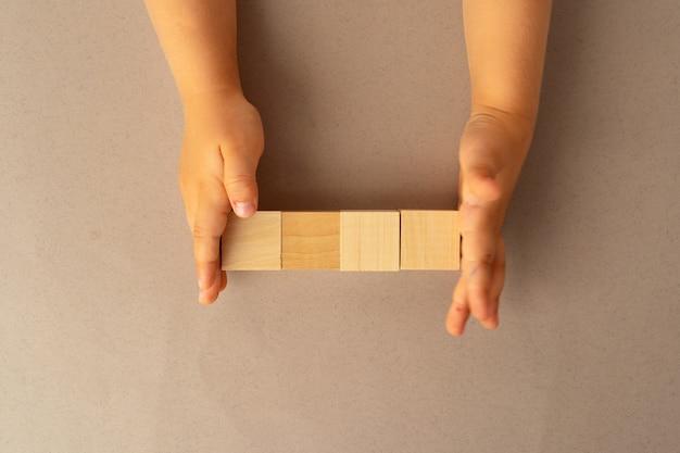 Ręce dziecka z czterema drewnianymi klockami, widok z góry