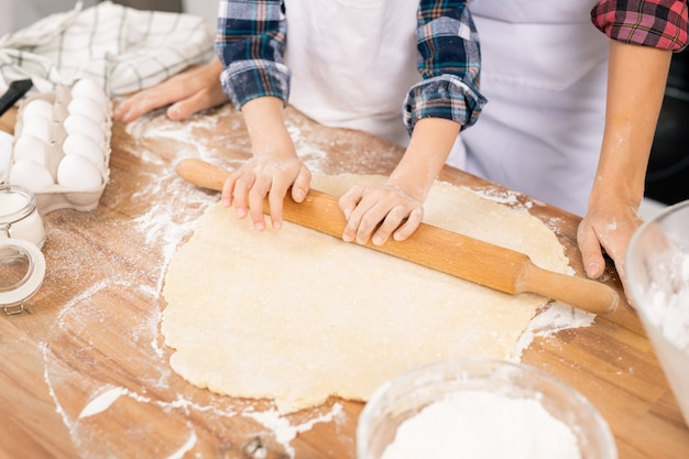Ręce dziecka z drewnianą szpilką toczenia świeżego ciasta na stole, pomagając mamie w gotowaniu ciasta