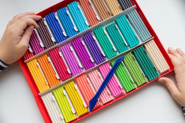 Ręce dziecka z kolorową gliną. maluch bawi się i tworzy zabawki z ciasta do zabawy, modelowanie modelarskie