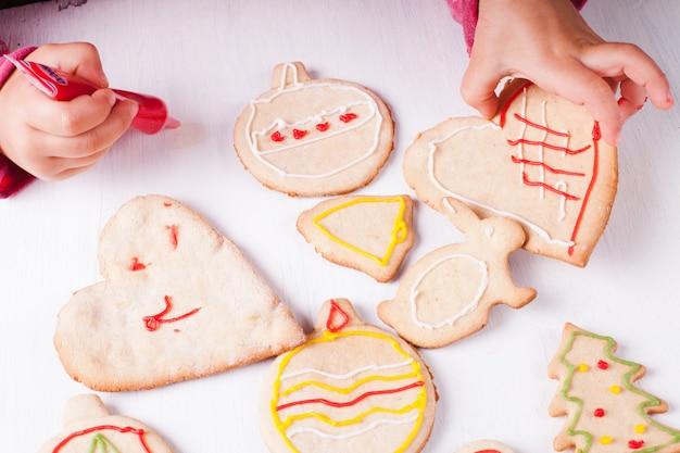 Ręce dziewczynki, która rysuje na piernikowych ciasteczkach