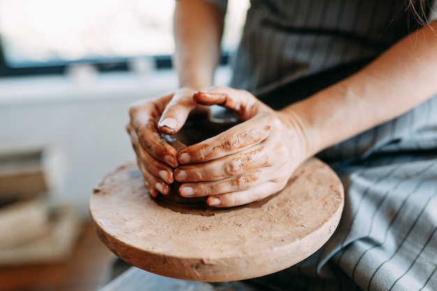 Ręce dziewczynki na kole garncarskim z gliną. proces tworzenia ceramiki.
