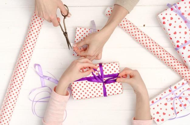 Ręce dziewczynki zdobią jasne pudełka na prezenty jedwabnymi wstążkami na urodziny, walentynki, boże narodzenie, nowy rok