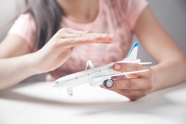 Ręce dziewczyny chronią model samolotu. podróżować