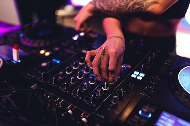 Ręce dziewczyny dj przy panelu sterowania muzyką