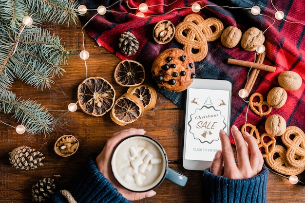 Ręce dziewczyny o gorący napój i przewijanie w smartfonie, idąc do sklepu internetowego podczas świątecznej wyprzedaży