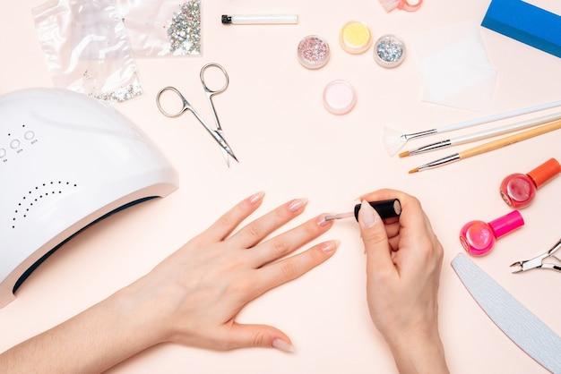 Ręce dziewczyny robi manicure w domu, zbliżenie rąk. widok z góry