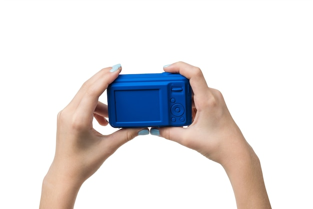 Ręce dziewczyny trzymają niebieski aparat na białym tle. sprzęt do strzelania.