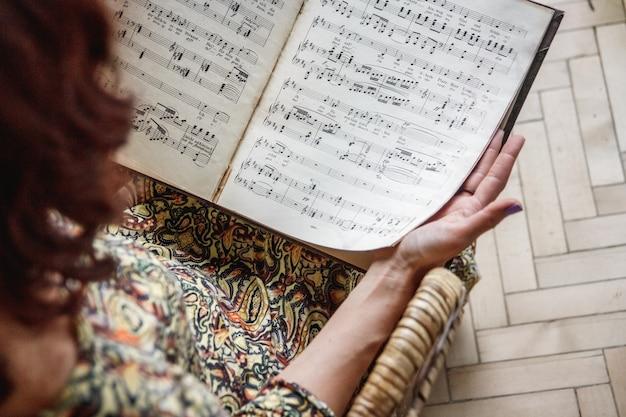 Ręce dziewczyny trzymają nuty fortepianu. selektywne skupienie.