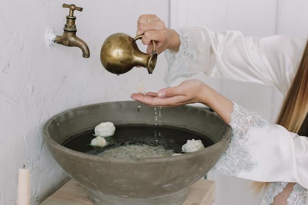 Ręce dziewczyny trzymającej kwiaty w starej umywalce z wodą