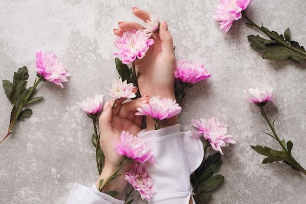 Ręce dziewczyny z delikatnym manicure w kwiaty