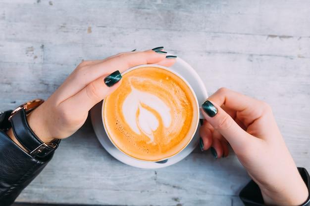 Ręce dziewczyny z lakierowanymi paznokciami wokół kubka widok z góry filiżanki kawy z pianką