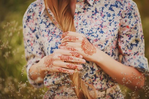 Ręce dziewczyny z rysunkami mehendi w stylu boho. miękka selektywna ostrość.