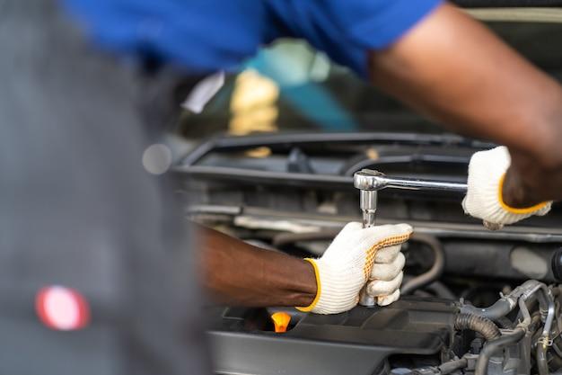 Ręce ekspertyza mechanika samochodowego w serwisie samochodowym. koncepcja konserwacji samochodów i serwisu samochodowego.