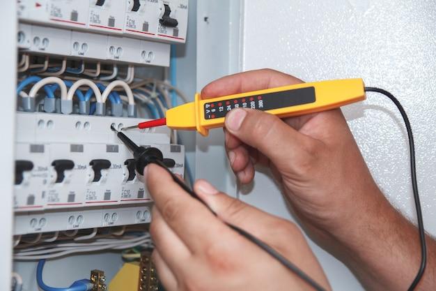 Ręce elektryka z sondą multimetrową w szafie rozdzielnicy elektrycznej badającej skrzynkę bezpiecznikową