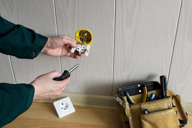 Ręce elektryków instalujące wbudowane gniazdo w ścianie i torbie z narzędziami znajdującymi się na podłodze