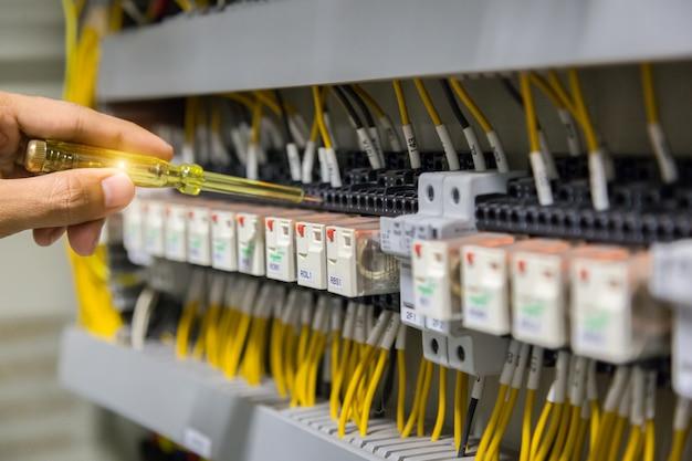 Ręce elektryków testujących prąd elektryczny w panelu sterowania.