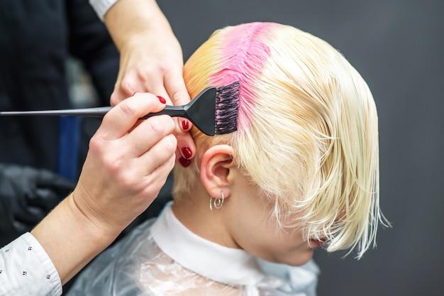 Ręce fryzjera farbują włosy na różowo, z bliska.