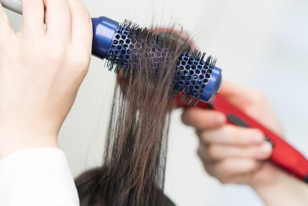 Ręce fryzjera suszy brunetka włosów klienta za pomocą niebieskiej szczotki do włosów i czerwonej suszarki do włosów w profesjonalnym salonie kosmetycznym.