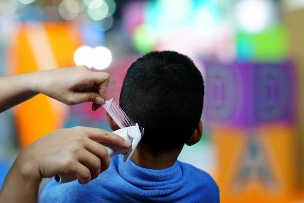 Ręce fryzjerka strzyżenia włosów małego chłopca za pomocą grzebienia i maszynki do strzyżenia w pięknym zakładzie fryzjerskim.
