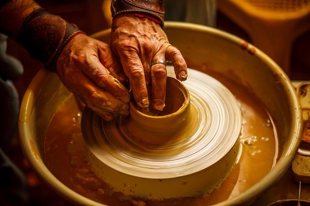 Ręce garncarza przygotowujące gliniany garnek. zbliżenie.