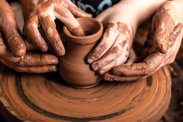 Ręce garncarza robi gliniany garnek na tle