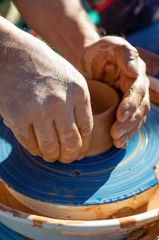 Ręce garncarza, tworząc gliniany słoik na kole