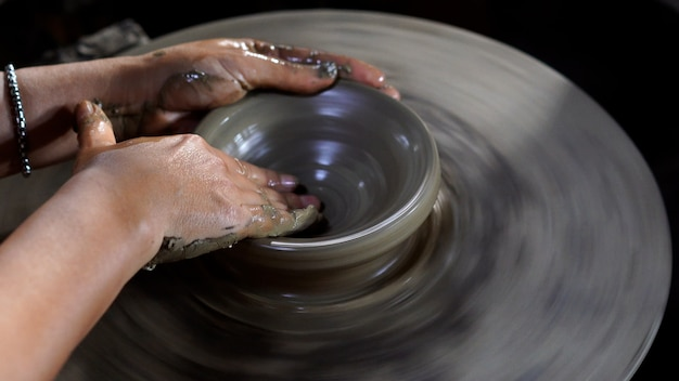 Ręce garncarzy tworzą na kole słoik lub wazon z ceramiki