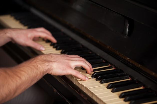 Ręce geniusza. zbliżenie dłoni dotykających klawiszy fortepianu