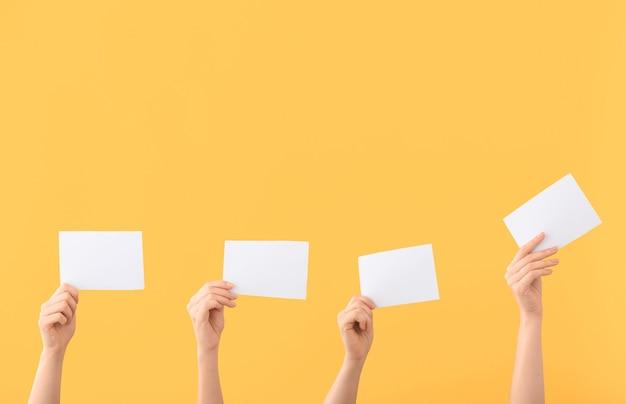 Ręce głosujących osób z kartami do głosowania na kolor