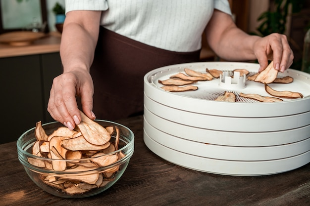 Ręce gospodyni wyjmującej plasterki suszonej gruszki z tacy suszarki do owoców i wkładającej je do szklanej miski, stojąc przy kuchennym stole
