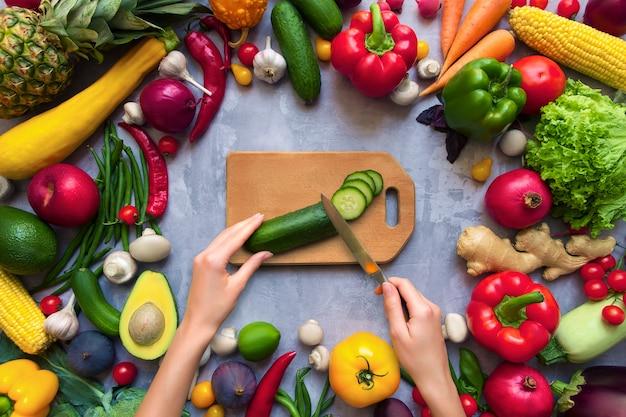 Ręce gotować zdrowe kolorowe przyprawy korzenne o smaku świeżych owoców i warzyw organicznych przeciwutleniaczy na przepisy wegańskie lub wegetariańskie na białym tle na szarym tle. pojęcie zdrowego stylu życia