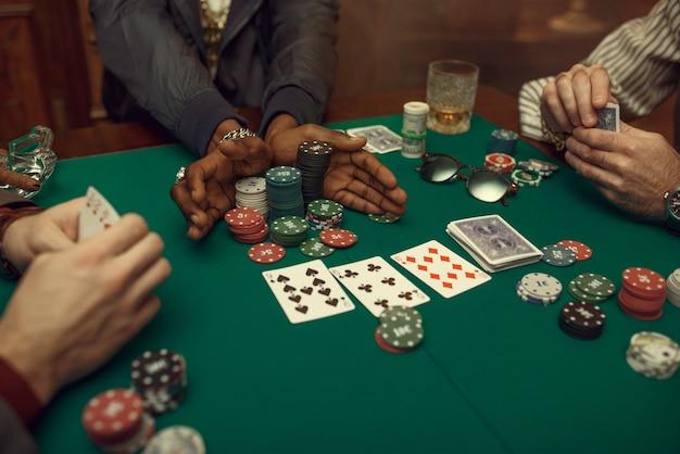 Ręce graczy w pokera, stół do gry