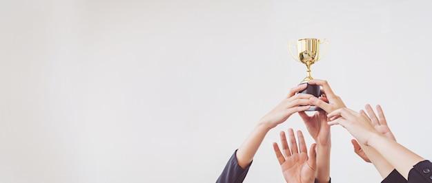 Ręce gramolą się o złoty puchar trofeum, biznes koncepcyjny