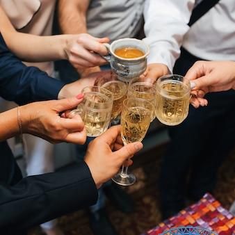 Ręce grupy przyjaciół brzęczących szklanki napoju alkoholowego oraz opiekania i gratulacji