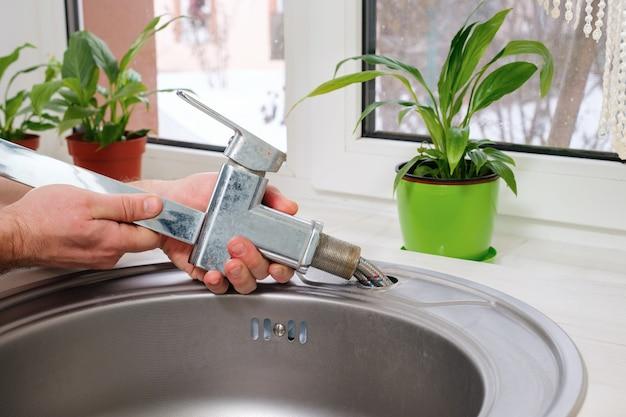 Ręce hydraulika wyjmują stary kran ze zlewu kuchennego