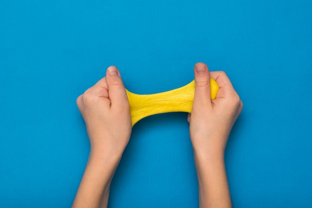 Ręce i jasnożółty szlam na niebieskim tle. zabawka antystresowa. zabawka do rozwoju motoryki ręcznej.