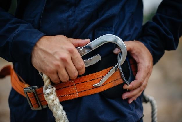 Ręce i pas pracownika stolarza w zbliżenie w odzieży roboczej iz paskiem. energia.