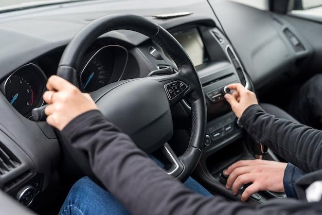 Ręce instruktora pomagają kierowcy prowadzić samochód